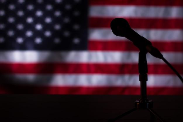 Amerykańska flaga w ciemności. mikrofon i flaga w ciemności. scena po koncercie. pokaz już się zakończył.