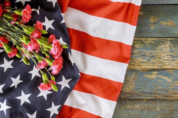Amerykańska flaga w dzień pamięci honoruje patriotyczny wojskowy usa w różowym goździku