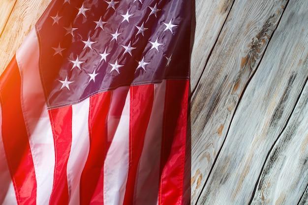 Amerykańska flaga w słońcu. flaga na białym tle drewnianych. sztandar wielkiego kraju. wolność i równość.