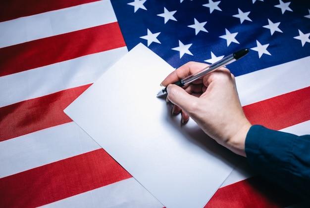 Amerykańska flaga z dolarami na nim. wybory w usa. kobieta kładzie kleszcza na papierze do głosowania. zmiany polityczne w kraju. skopiuj miejsce.