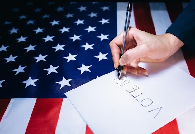 Amerykańska flaga z dolarami na nim. wybory w usa. kobieta kładzie kleszcza na papierze do głosowania. zmiany polityczne w kraju.