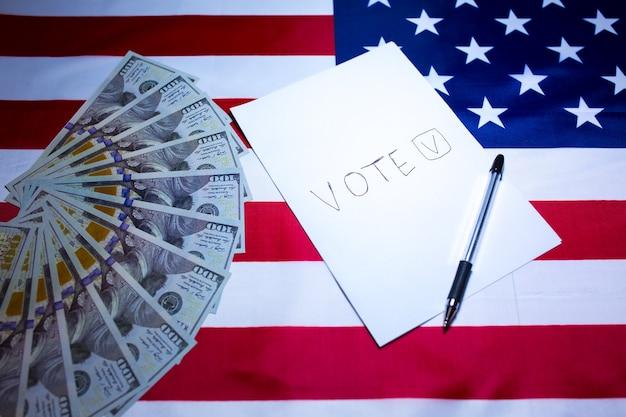 Amerykańska flaga z dolarami na nim. wybory w usa. papier do kleszcza głosowania. pieniądze jako pojęcie korupcji. niesprawiedliwe zmiany polityczne w kraju.