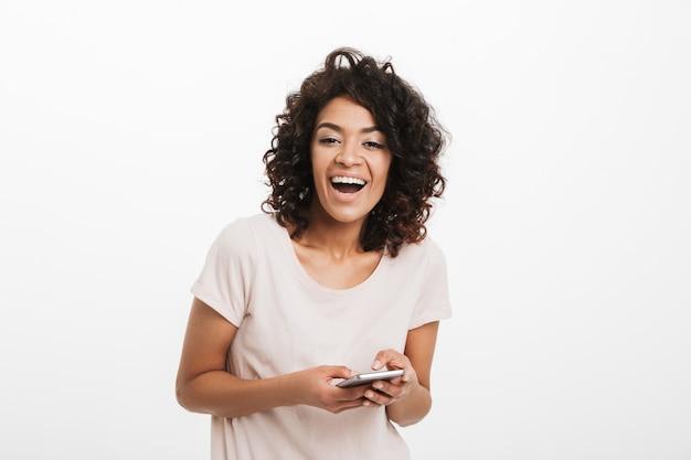 Amerykańska kobieta 20s z kręconymi włosami, trzymając telefon komórkowy i uśmiechnięty, odizolowane na białej ścianie