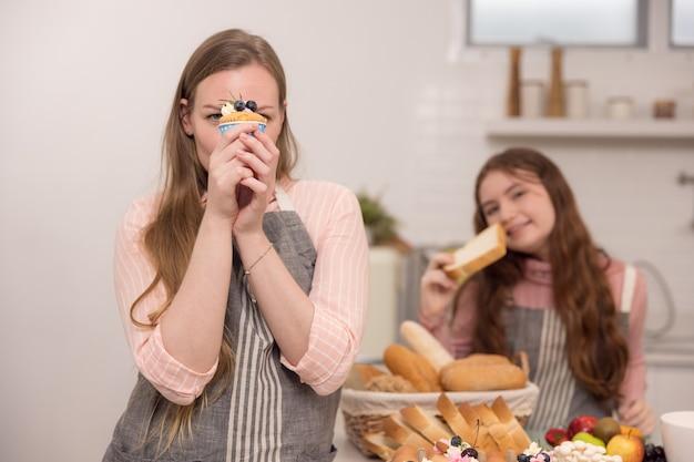 Amerykańska matka i córka trzymają babeczki i uśmiechają się do siebie
