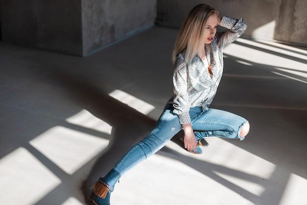 Amerykańska młoda blondynka w stylowej koszuli w vintage zgrywanie dżinsów w modnych kowbojskich butach pozowanie, siedząc w pomieszczeniu z promieniami słonecznymi
