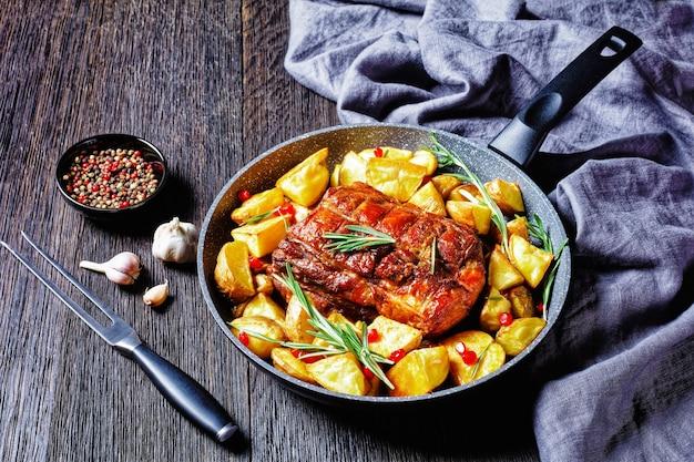 Amerykańska niedzielna pieczona kolacja: schab pieczony z pieczonymi łódeczkami ziemniaczanymi z rozmarynem podany na żeliwnej patelni z czosnkiem i pieprzem na ciemnym drewnianym tle, widok z góry, zbliżenie
