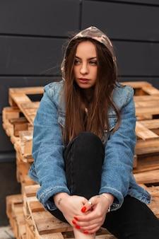 Amerykańska nowoczesna dość stylowa młoda kobieta w modnych dżinsowych ubraniach młodzieżowych z wojskowym kapturem pozowanie na drewnianych paletach na zewnątrz. miejski modna dziewczyna modelka odpoczynek w mieście. styl uliczny.