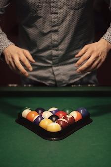 Amerykańska pula bilardowa. trójkąt kul bilardowych. mężczyzna przygotowuje się do gry w bilard.