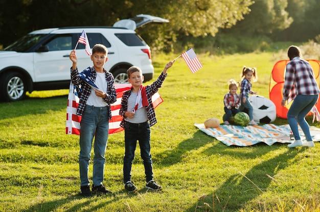 Amerykańska rodzina. matka i czwórka dzieci. z flagami usa. ameryka świętuje.