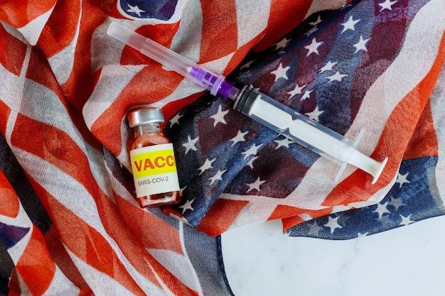 Amerykańska szczepionka w butelce i strzykawce do walki z zastrzykiem koronawirusa sars-cov-2 covid-19 z flagą usa