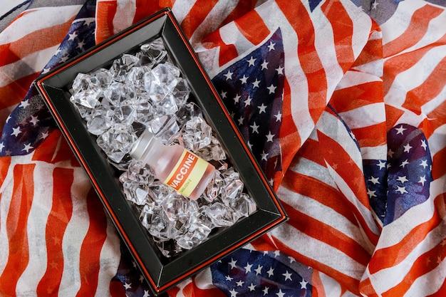 Amerykańska szczepionka w szklanych fiolkach z lekarstwami na lodzie, utrzymująca szczepionki w niskiej temperaturze do walki z koronawirusem covid-19, sars-cov-2 z flagą usa
