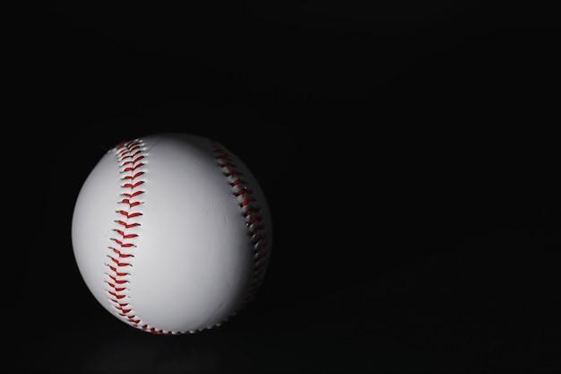 Amerykańska tradycyjna gra sportowa. baseball. pojęcie. piłka baseballowa i kije na czarnym stole.