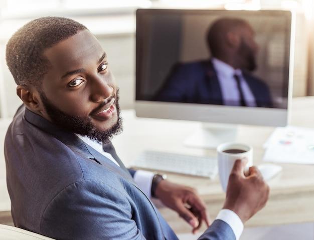 Amerykański biznesmen trzyma filiżankę kawy w klasycznym kostiumu