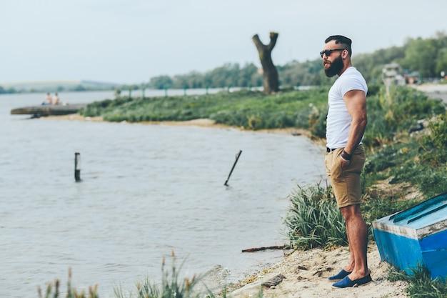 Amerykański brodaty mężczyzna wygląda na brzegu rzeki w niebieskiej kurtce