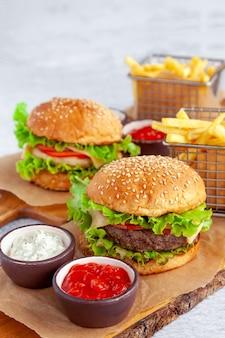 Amerykański burger wołowy z frytkami, bułką, kotletem wołowym, serem