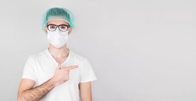 Amerykański chirurg lekarz mężczyzna na szarym tle, patrząc i wskazując w bok.