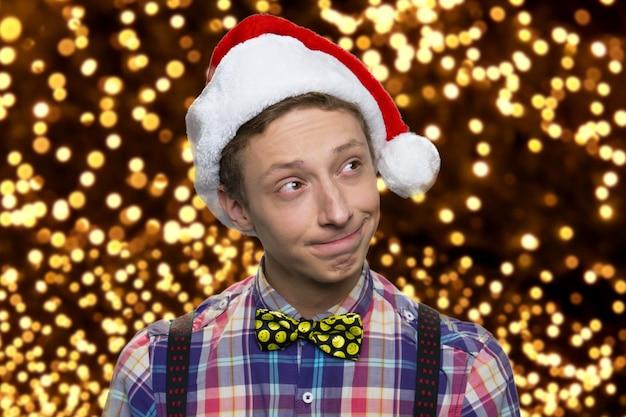Amerykański chłopiec nastolatek w santa hat. szczęśliwego nowego roku. tysiące świecących światełek w tle.