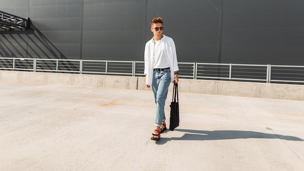 Amerykański fajny młody człowiek w stylowych ciuchach w czerwonych sandałach i materiałowej torbie w okularach przeciwsłonecznych jest na ulicy w pobliżu szarego budynku. modny facet na zewnątrz. nowa kolekcja letniej odzieży męskiej.