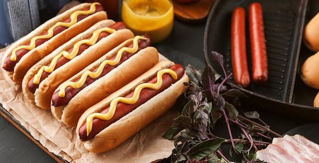Amerykański hot dog z składnikami na ciemnej drewnianej powierzchni