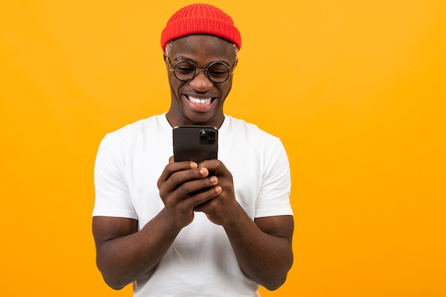 Amerykański mężczyzna uśmiecha się trzymający smartphone w jego rękach na kolorze żółtym z kopii przestrzenią