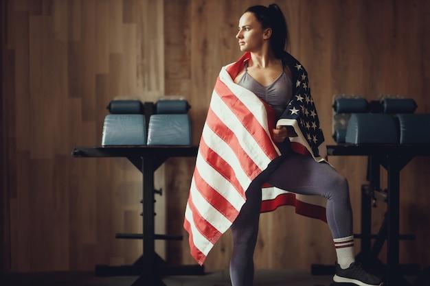 Amerykański patriota dziewczyna o atletycznej budowie ciała, pozowanie na tle drewnianej ściany pokrytej flagą usa