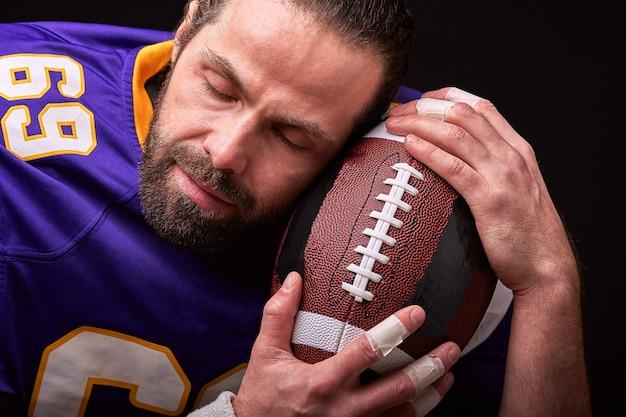 Amerykański piłkarz całuje piłkę