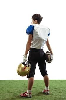 Amerykański piłkarz na białym tle na ścianie białego studia z copyspace. pojęcie sportu, ruchu, osiągnięć.