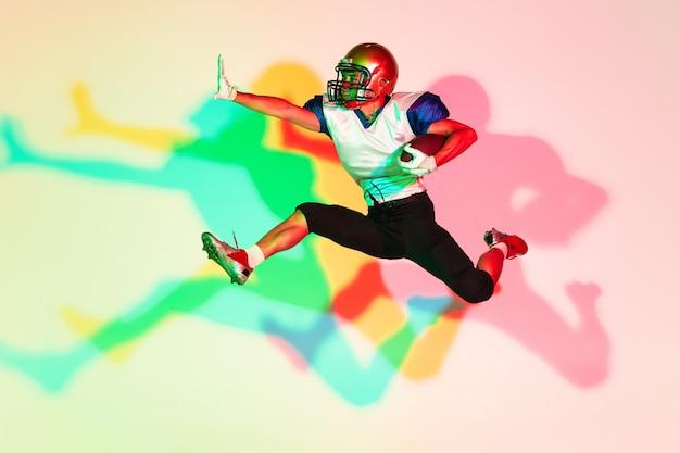 Amerykański piłkarz na gradientowym tle studyjnym w neonowym kolorze
