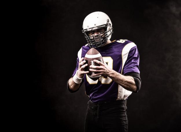 Amerykański piłkarz trzymając piłkę w dłoniach