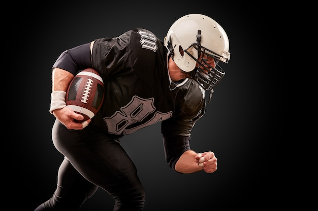 Amerykański piłkarz w ciemnym mundurze z piłką przygotowuje się do ataku na czarnym tle.