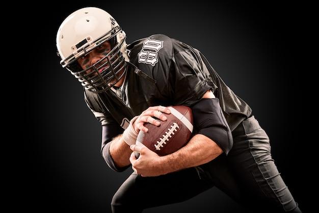 Amerykański piłkarz w ciemnym mundurze z piłką przygotowuje się do ataku