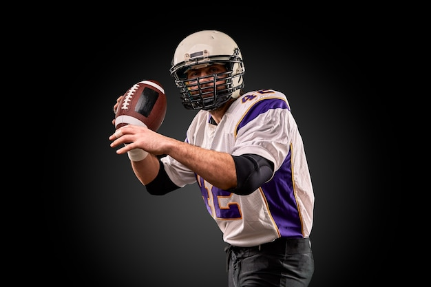 Amerykański piłkarz w mundurze z piłką przygotowuje się do podania koncepcja futbolu amerykańskiego czarne tło