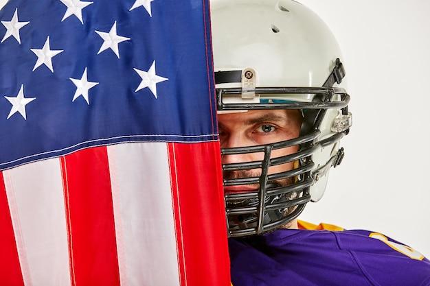 Amerykański piłkarz z mundurem i amerykańską flagą dumny ze swojego kraju, na białej przestrzeni.