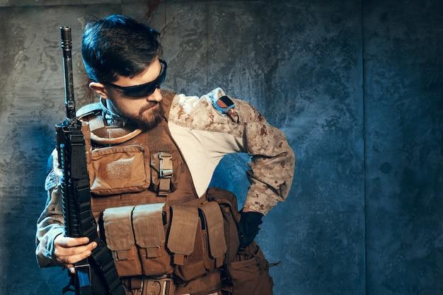 Amerykański prywatny wojskowy kontrahent trzyma karabin. obraz na ciemnym tle