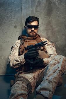 Amerykański prywatny wojskowy kontrahent trzyma karabin. obraz w ciemności