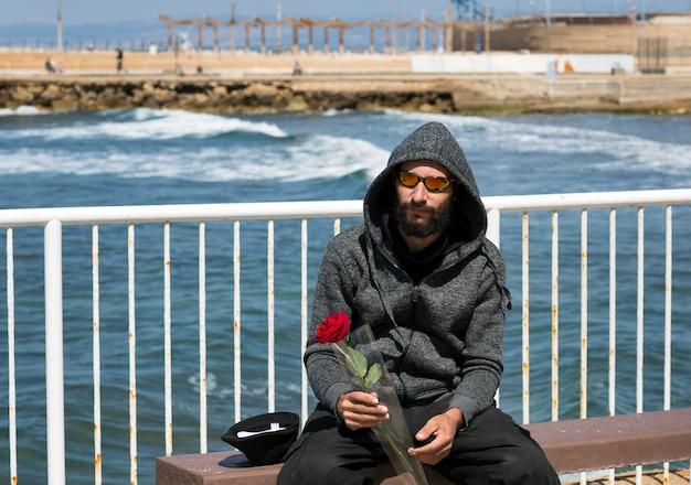 Amerykański przystojny brodaty mężczyzna nosi okulary przeciwsłoneczne i kurtka z kapturem przeciw błękitne morze w słoneczny dzień. rosyjski kaukaski brutalny koleś trzymający w ręku czerwony kwiat róży. romantyczne i walentynkowe wakacje