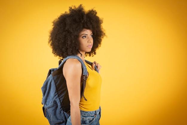 Amerykański student z plecakiem trzymając notebook na na białym tle żółtym tle