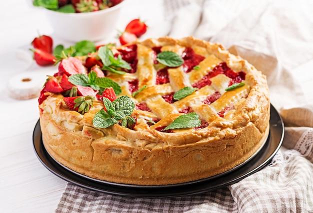 Amerykański truskawkowy pasztetowy tarta torta cukierki piec ciasto jedzenie na białym drewnianym stole.