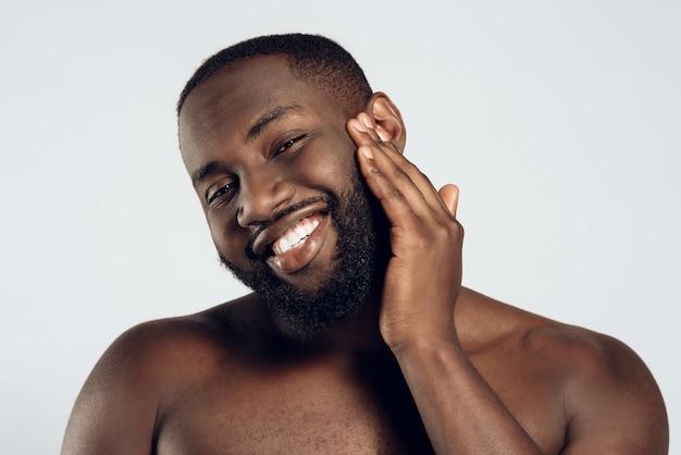Amerykański uśmiechnięty mężczyzna jest posmarowany kremem do twarzy.