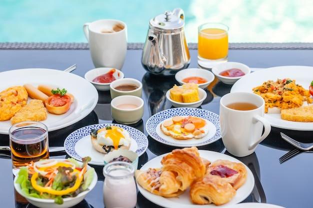 Amerykański zestaw śniadaniowy z czajnikiem na stole obok basenu w ośrodku. angielskie jedzenie rano w pobliżu basenu w luksusowym hotelu. letnie wakacje w tropikalnym kraju, tajlandia. podróżuj i zrelaksuj się