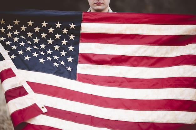Amerykański żołnierz trzymający amerykańską flagę