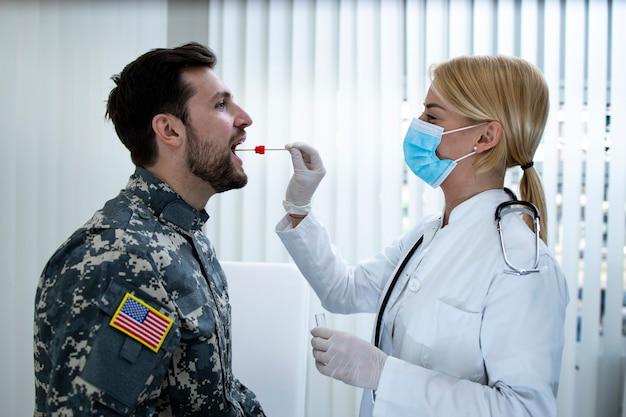 Amerykański żołnierz w mundurze wykonujący test pcr w gabinecie lekarskim podczas epidemii wirusa covid19