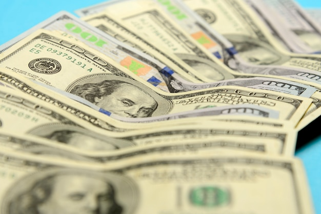 Amerykańskie 100 banknotów dolarowych określone na niebieskim tle