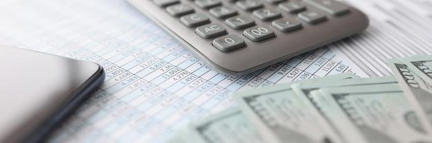 Amerykańskie banknoty wraz ze sprawozdaniem finansowym i kalkulatorem leżą na małym i średnim stole