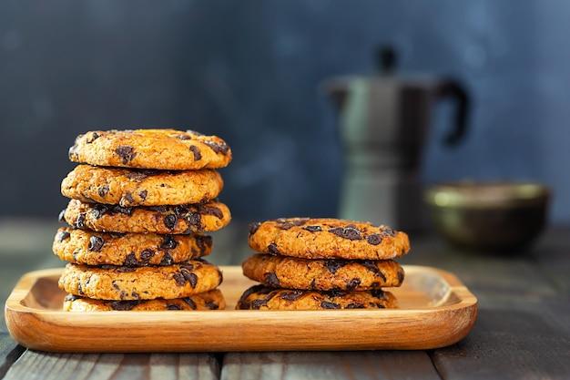 Amerykańskie ciasteczka z kawałkami czekolady na drewnianym talerzu i dzbanek do kawy na stole