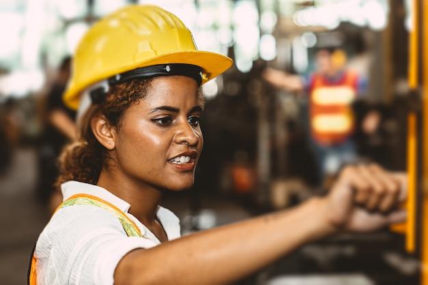 Amerykańskie czarne kobiety nastolatka pracująca w fabryce przemysłu z ciężką stalową maszyną.