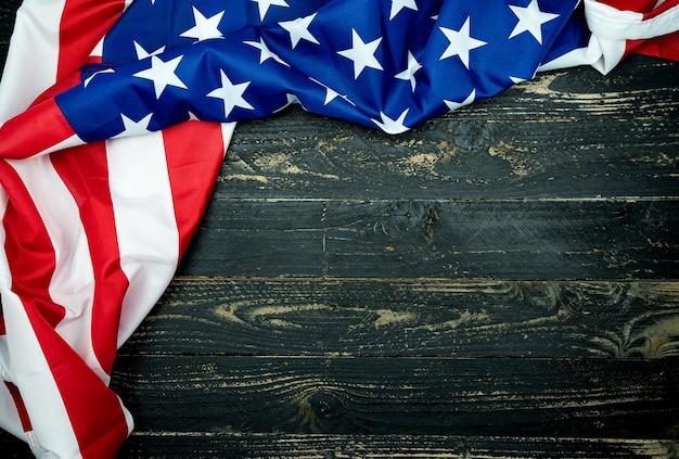 Amerykańskie flagi na czarnym tle drewna, obraz na 4 lipca dzień niepodległości flaga usa na tle ciemnej ściany drewnianej.
