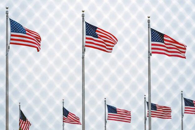 Amerykańskie flagi przy waszyngtońskim pomnikiem za drucianym ogrodzeniem.