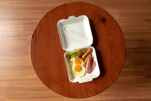 Amerykańskie śniadanie w stylu zestawu pudełkowego. mały posiłek składający się z szynek i jajek sadzonych