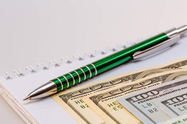 Amerykańskie sto dolarowe banknoty. długopis i notatnik obok rachunków. biznes i finanse. pieniądze. białe tło.